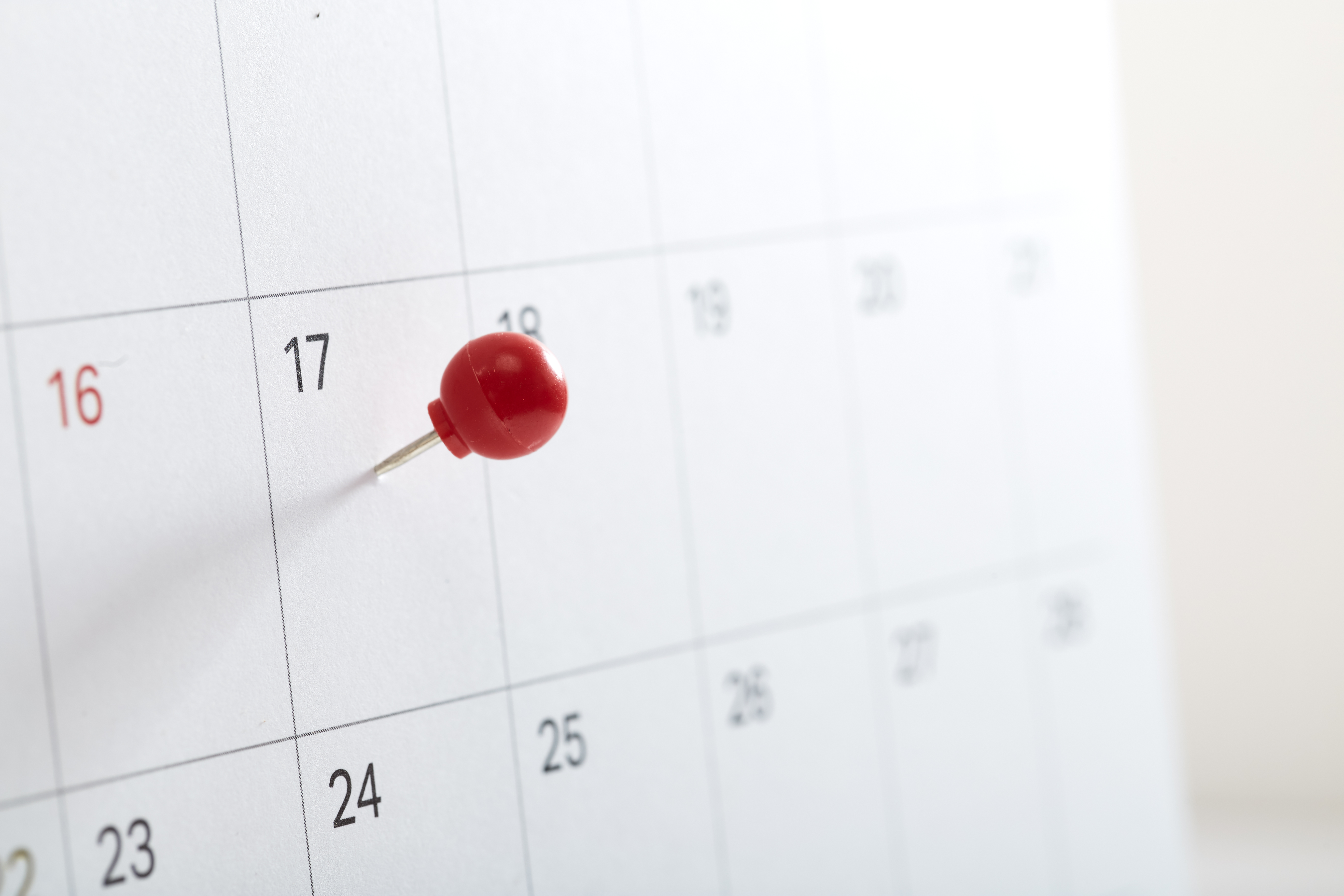 A red pin on calendar to remind about the appointment, Tax Day 2018 takes place on April 17, 2018