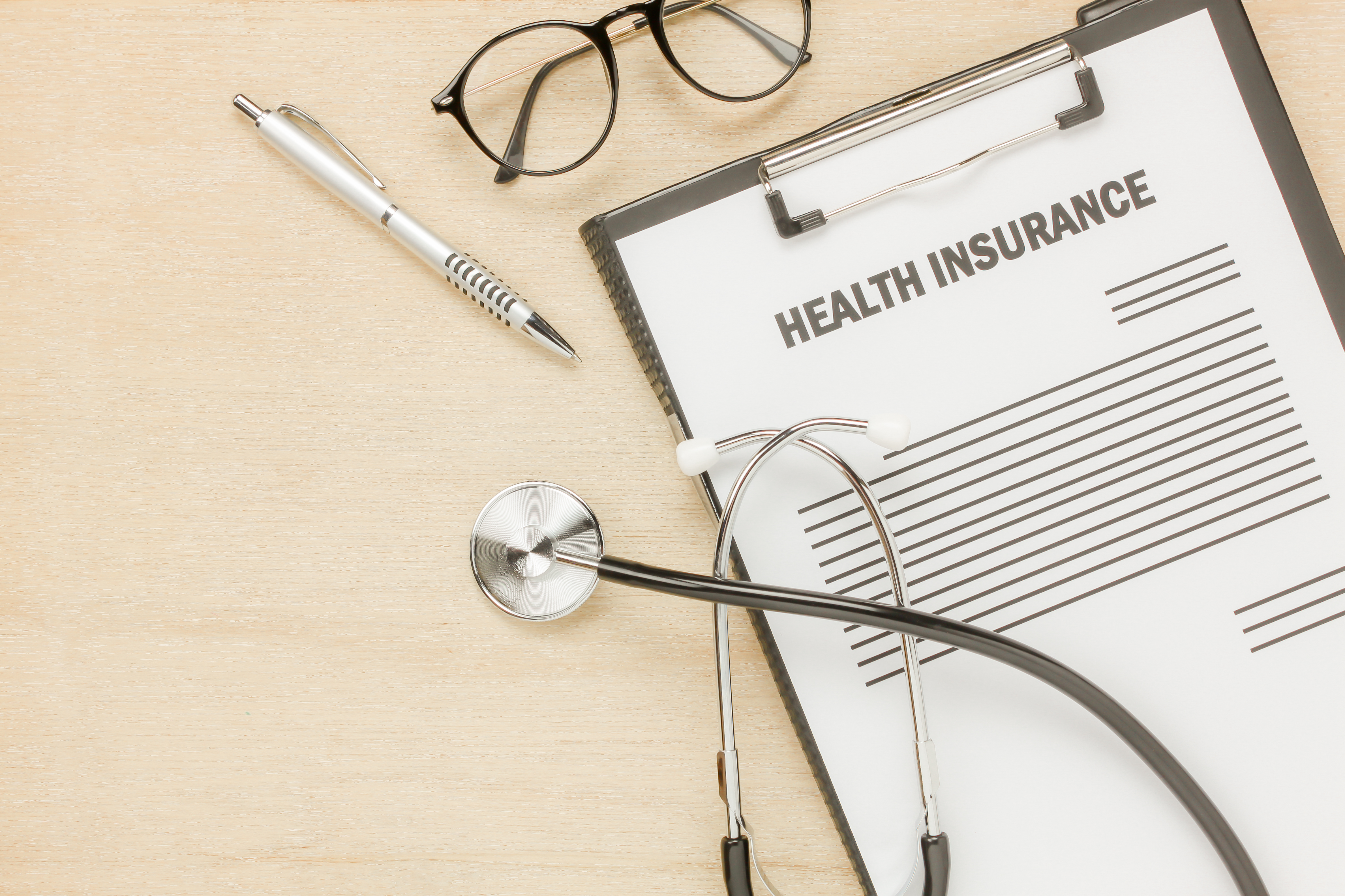 Top view health insurance form and eyeglasses with stethoscope on wooden background.business and healthcare concept.savings.flat lay.copy space.