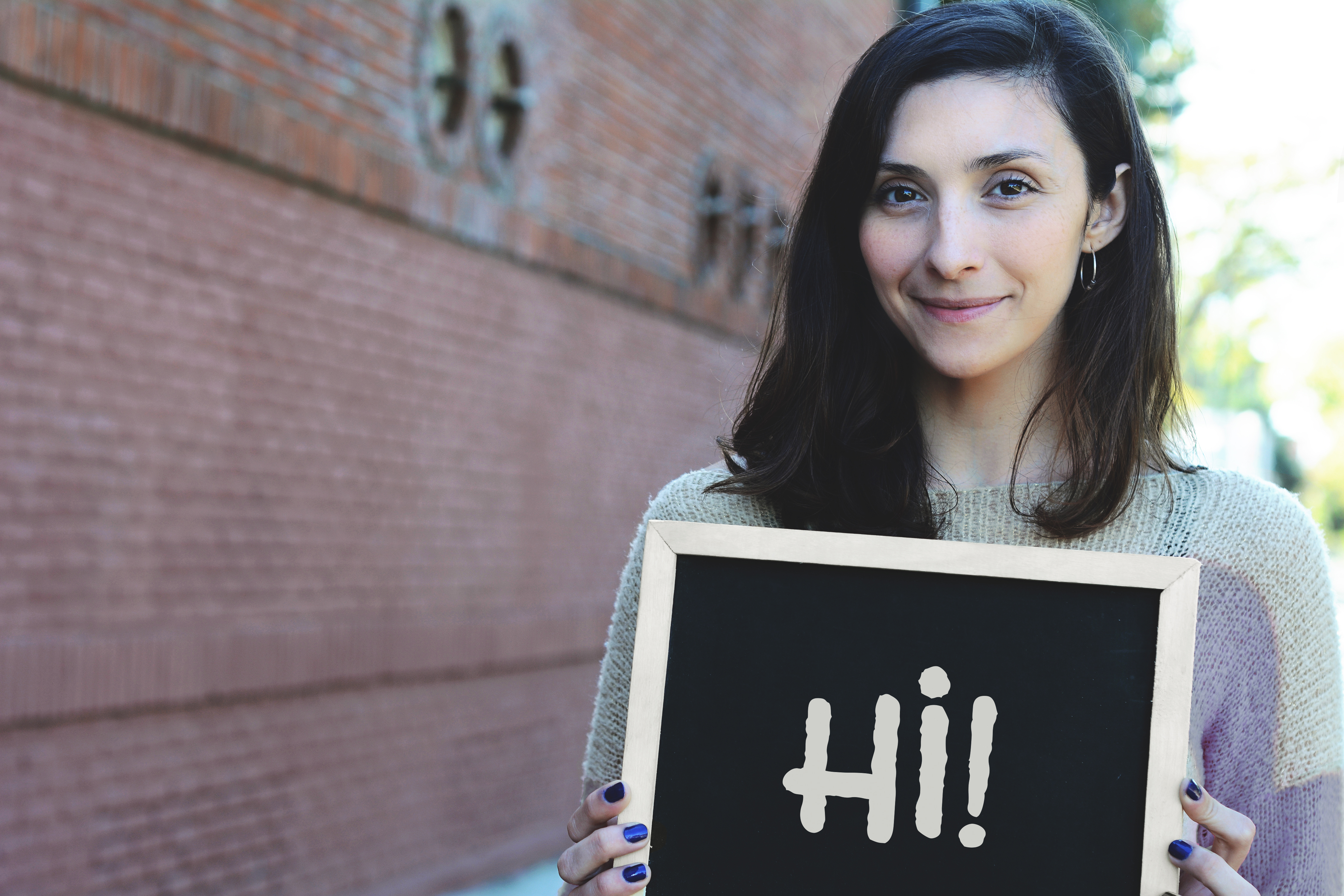 "Young beautiful woman holding chalkboard with text ""hi"". Outdoors."