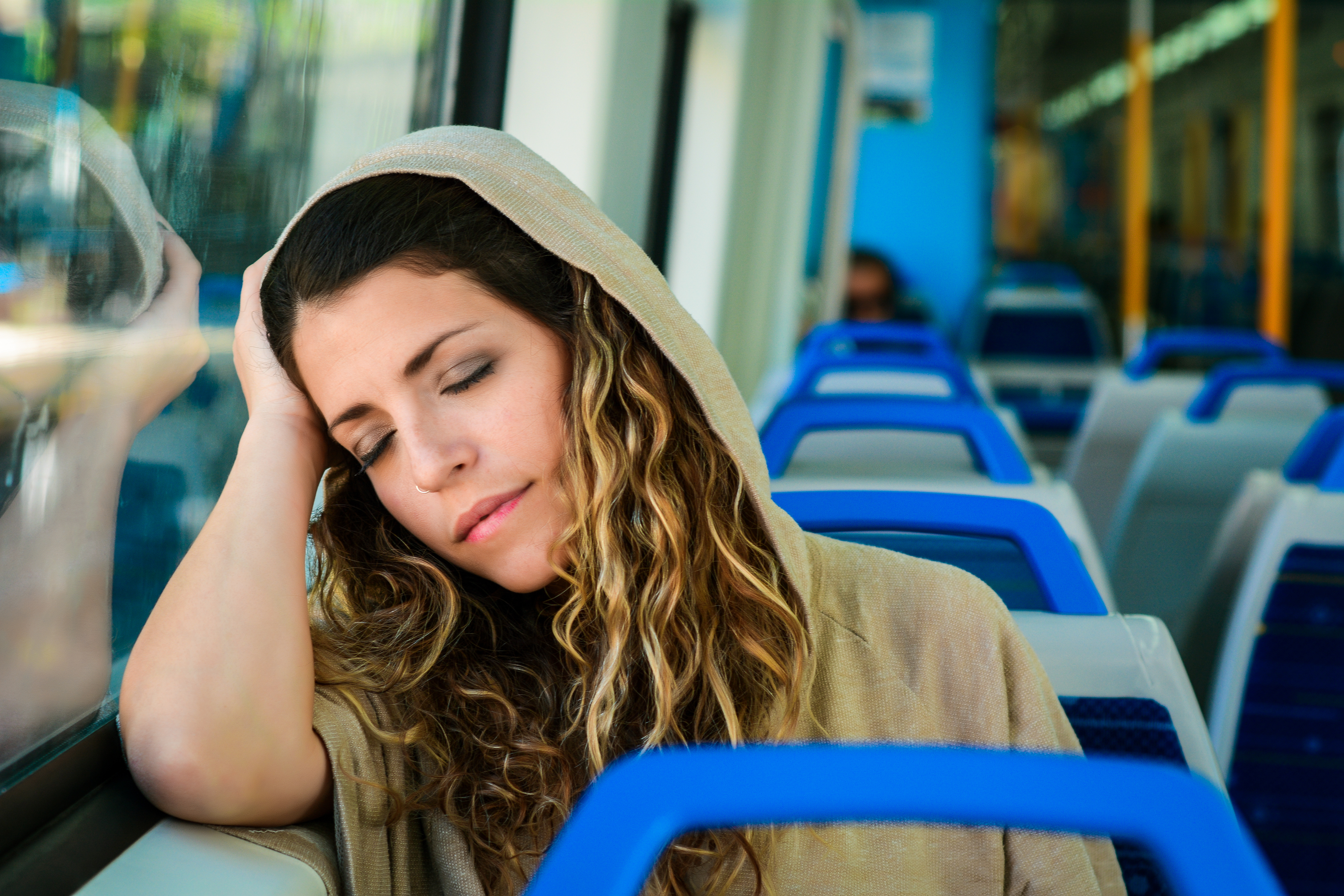 Young urban woman sleeping in a train travel beside the window. Modern people city lifestyle.